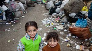 "Two children posing in front of garbage piles. Source: A Youtube video entitled"" The Zabbaleen of Garbage City."""